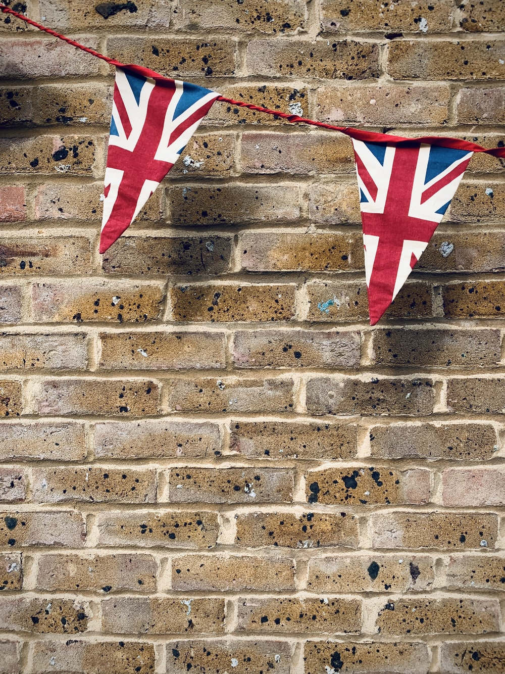red and white star flag on brown brick wall