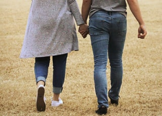 man and woman holding hands while walking on brown field during daytime