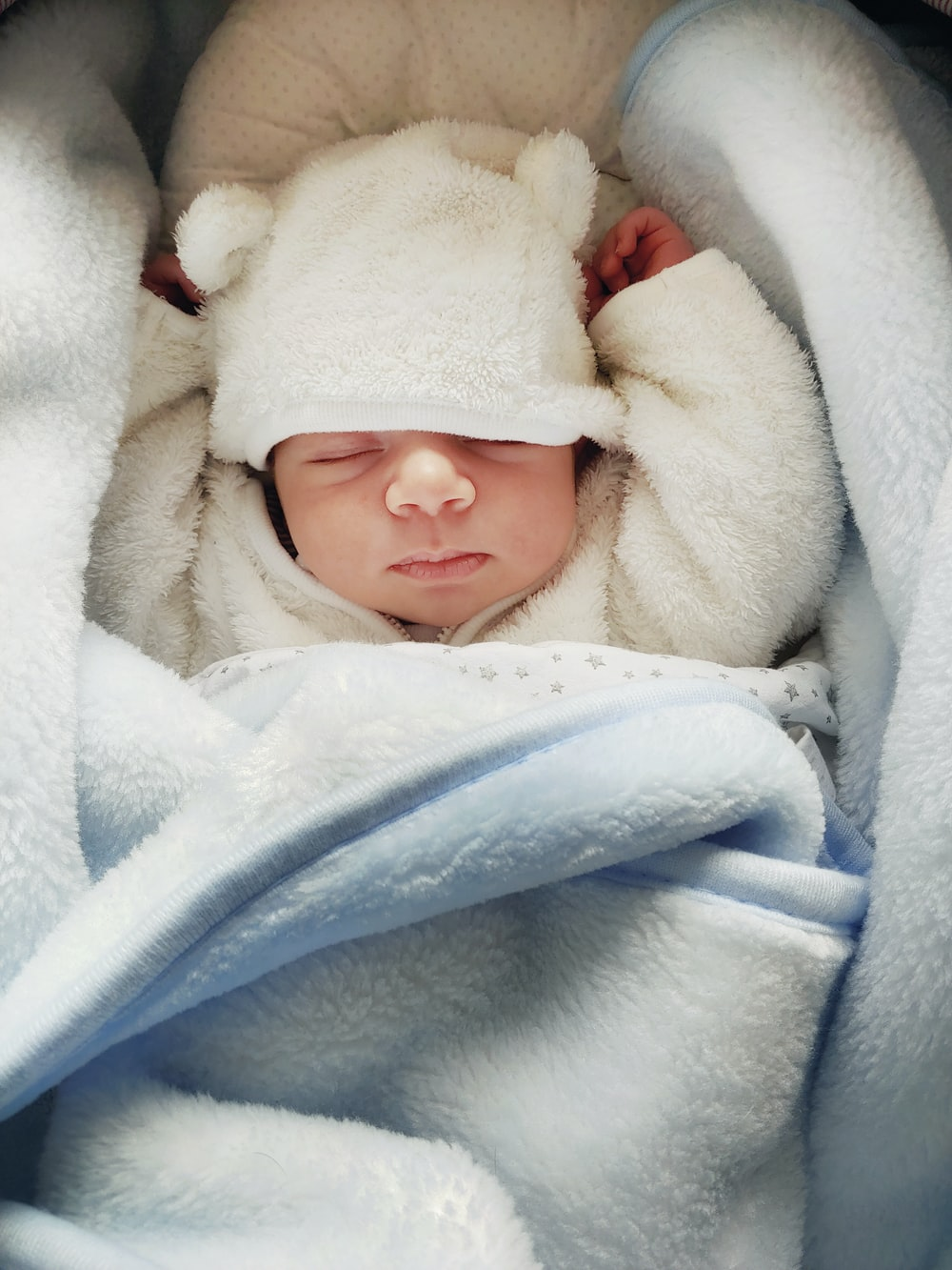 baby covered with white blanket