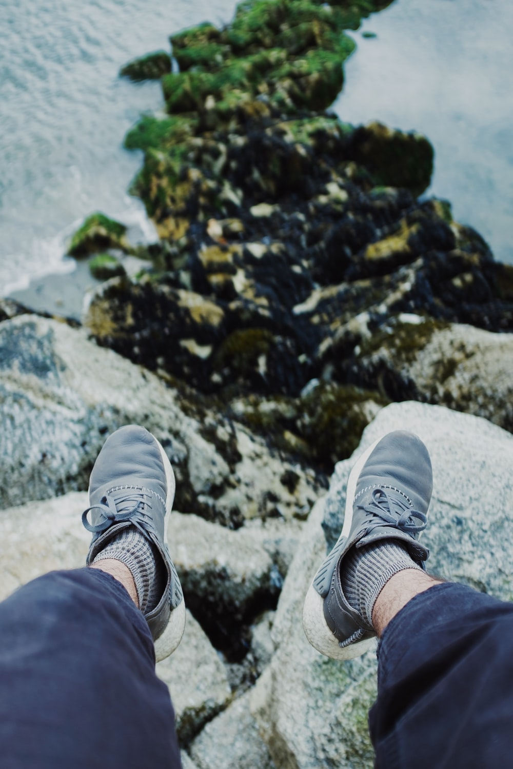 person in blue pants and white sneakers sitting on rock