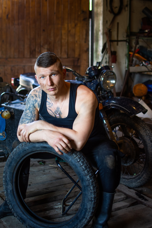 man in black tank top sitting on motorcycle