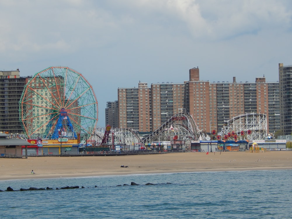 people on beach near ferris wheel during daytime