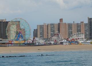people on beach near ferris wheel during daytime