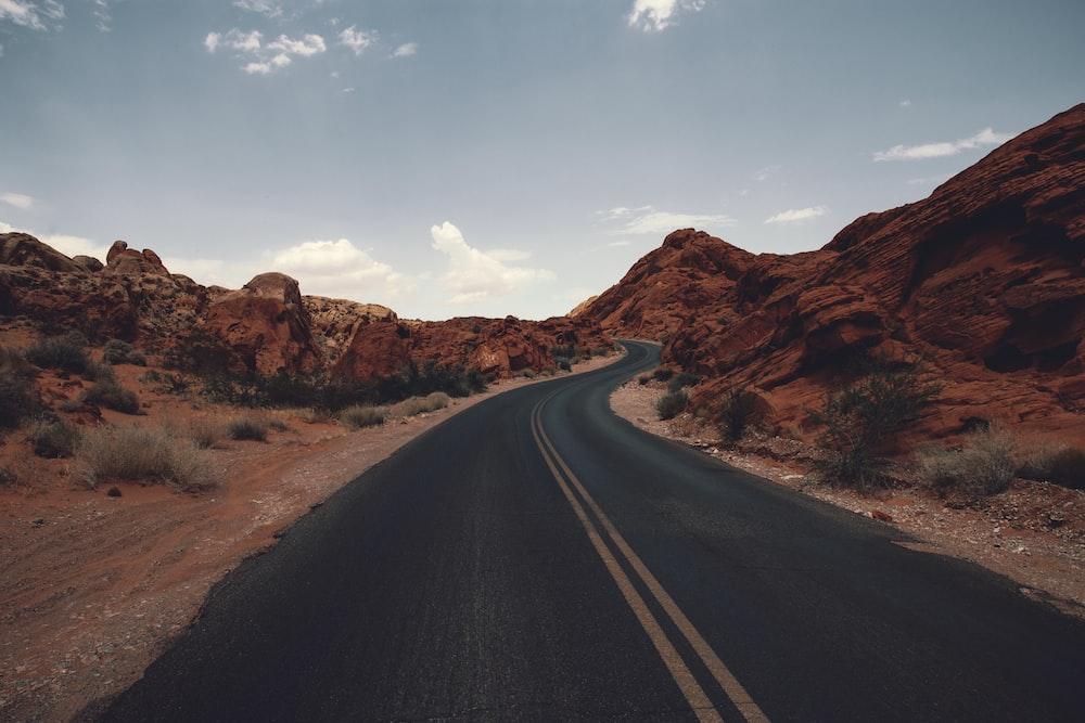 black asphalt road between brown rock formation under blue sky during daytime
