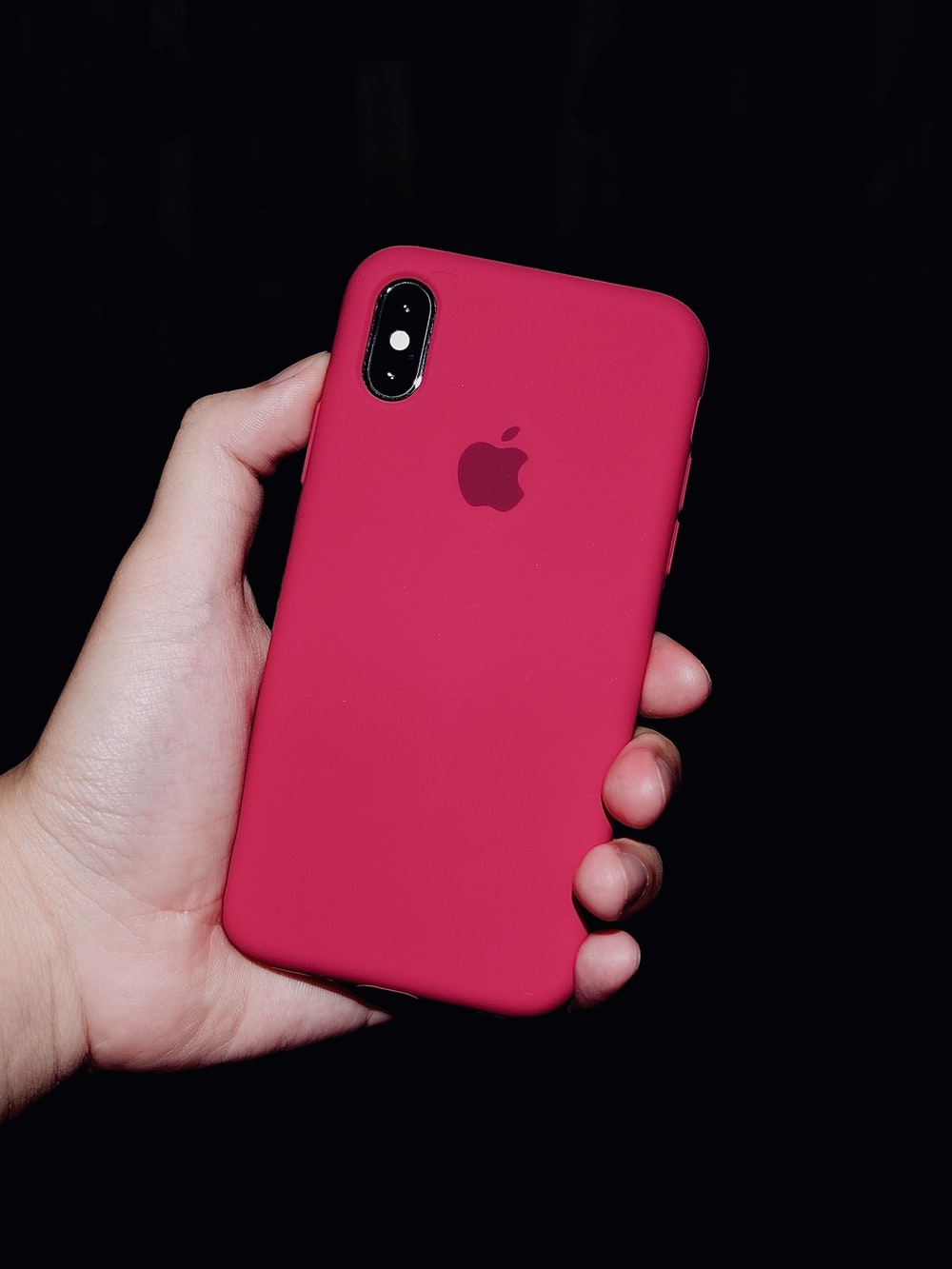 person holding iphone with red case