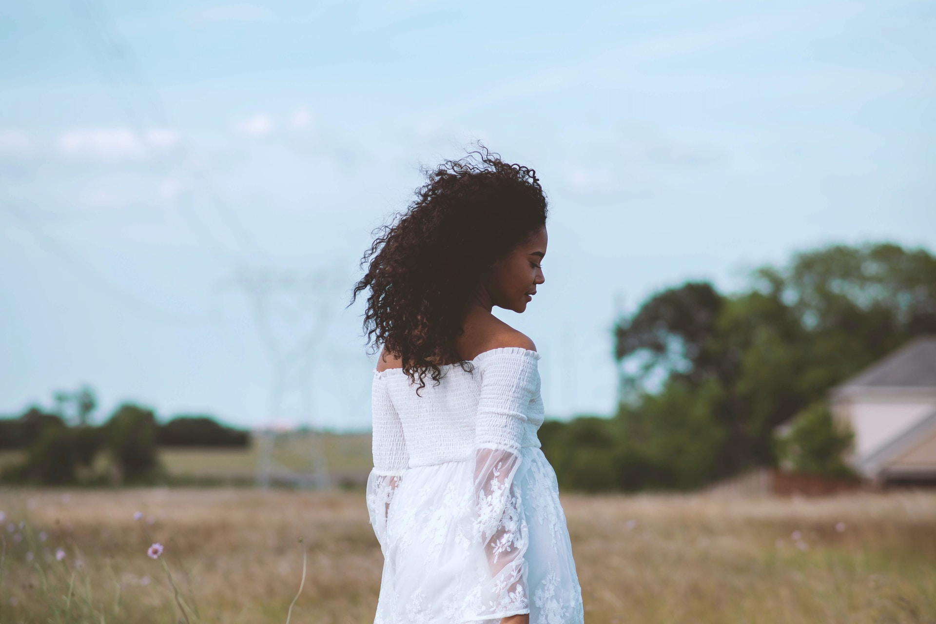 girl in white dress standing on green grass field during daytime