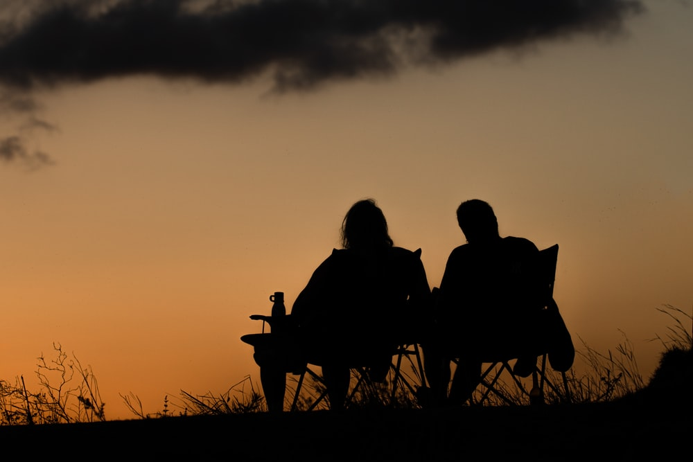 silhouette of 2 person sitting on bench during sunset
