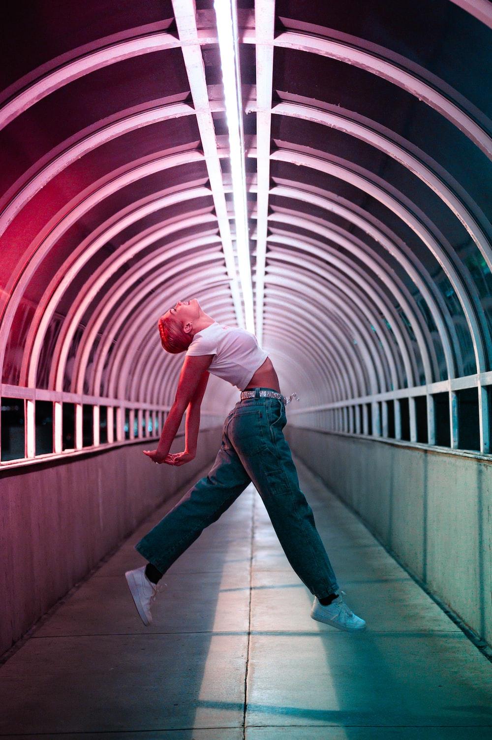 man in blue denim jeans and white shirt standing on white floor tiles