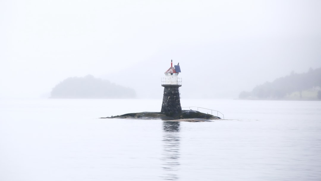 A small beacon on an island standing alone in the wide white fog of the day. Always on duty.  Can be seen from a car ferry between Åfarnes and Sølsnes (Norway).