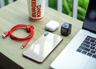white and red disposable cup beside black and silver laptop computer on brown wooden table