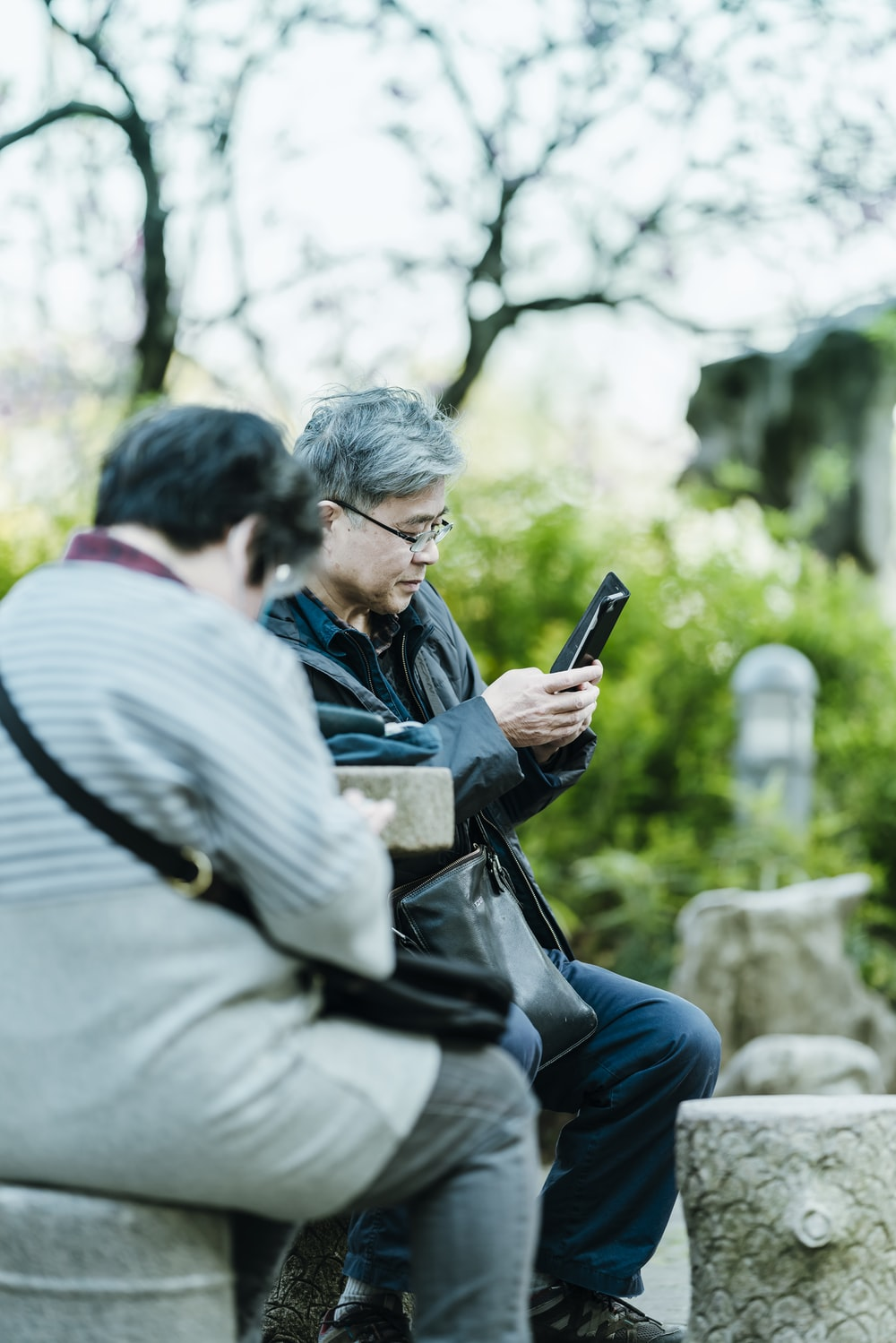 man in black jacket holding black smartphone