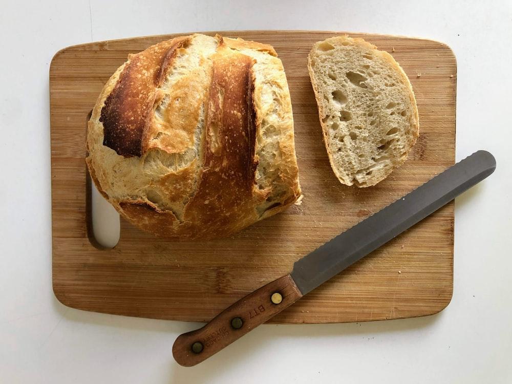 bread on brown wooden chopping board beside silver knife