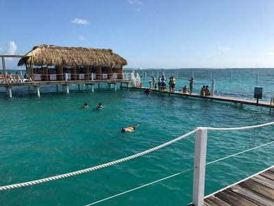 people swimming on sea near brown wooden beach house during daytime dominican republic teams background