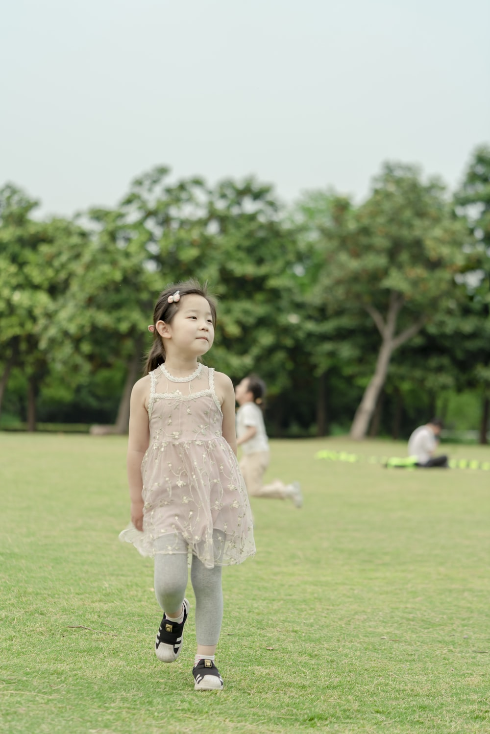 girl in white floral dress standing on green grass field during daytime