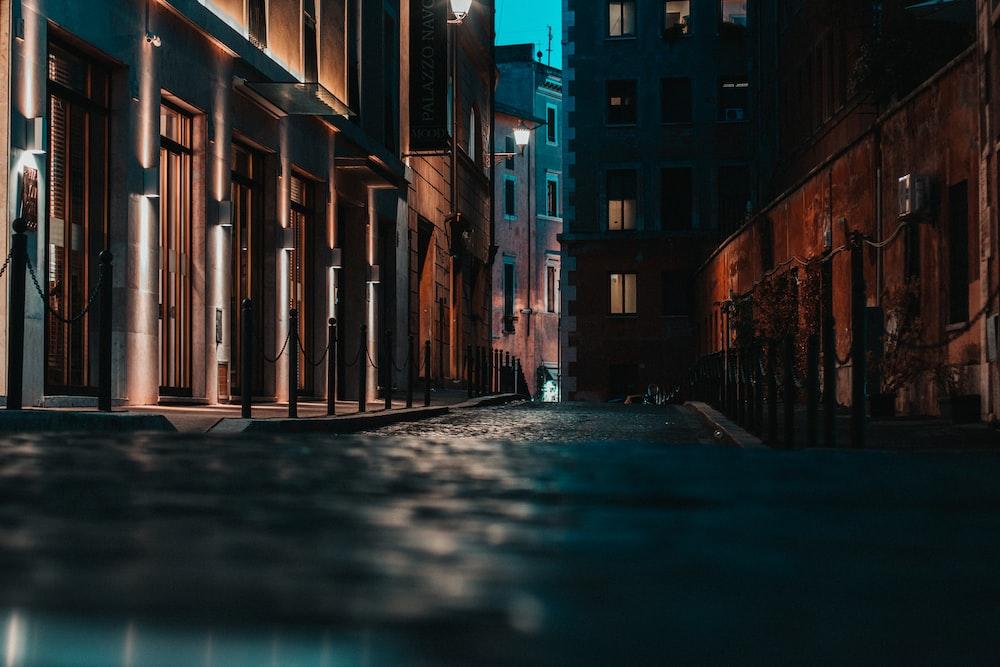 empty street between brown concrete buildings during daytime