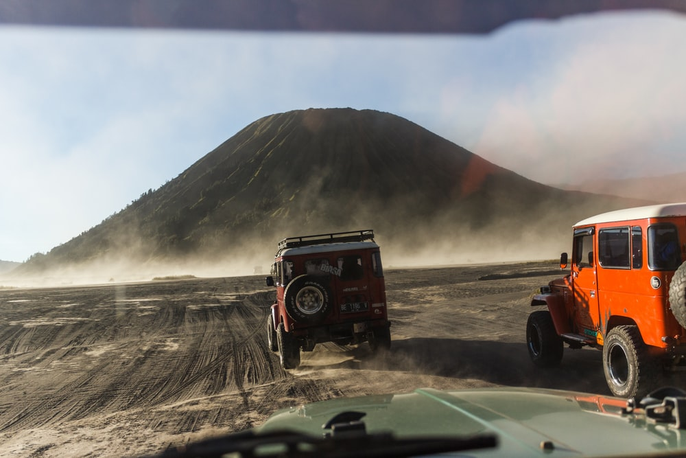 red and black jeep wrangler on dirt road during daytime