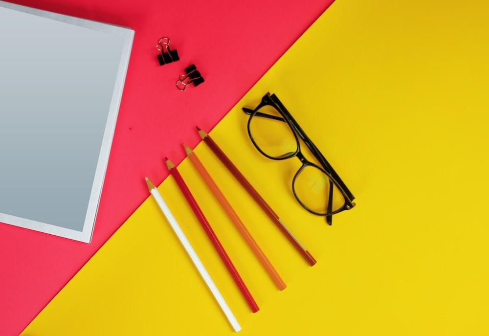 black framed eyeglasses on yellow paper