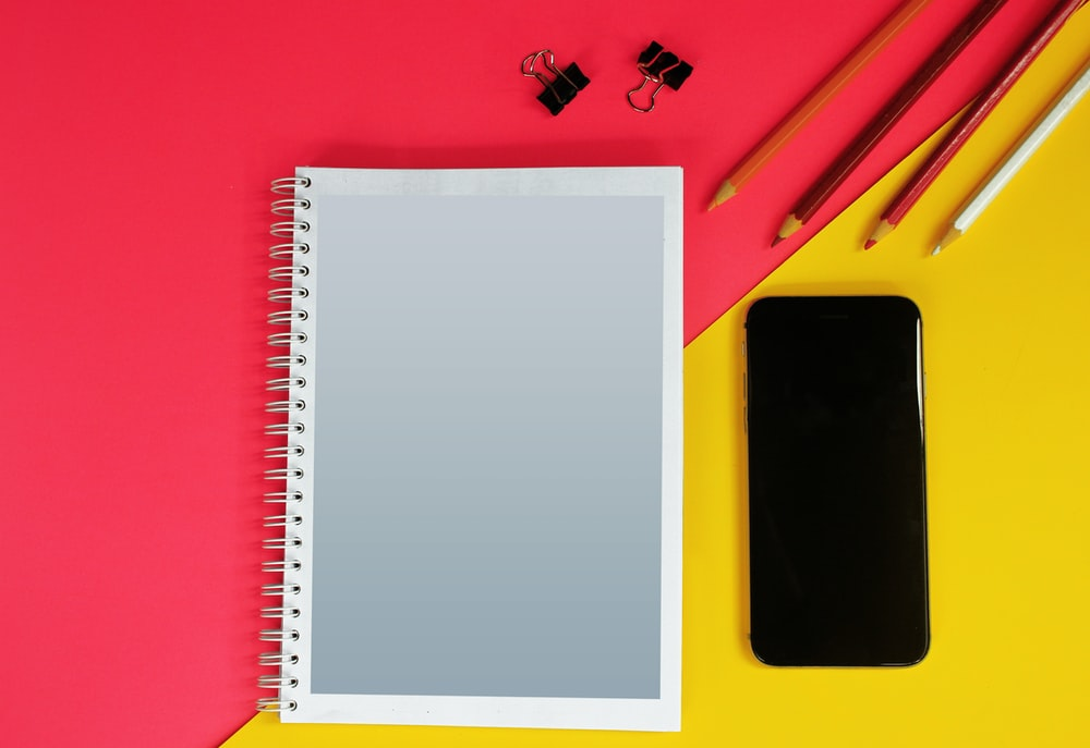 white notebook on red table