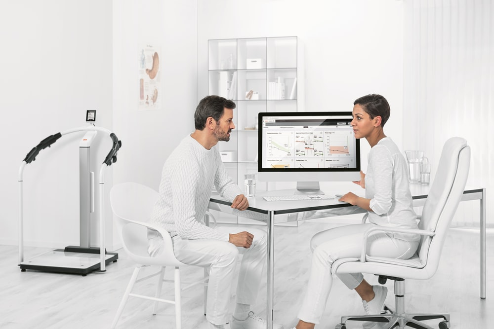 man in white dress shirt sitting on white chair in front of computer