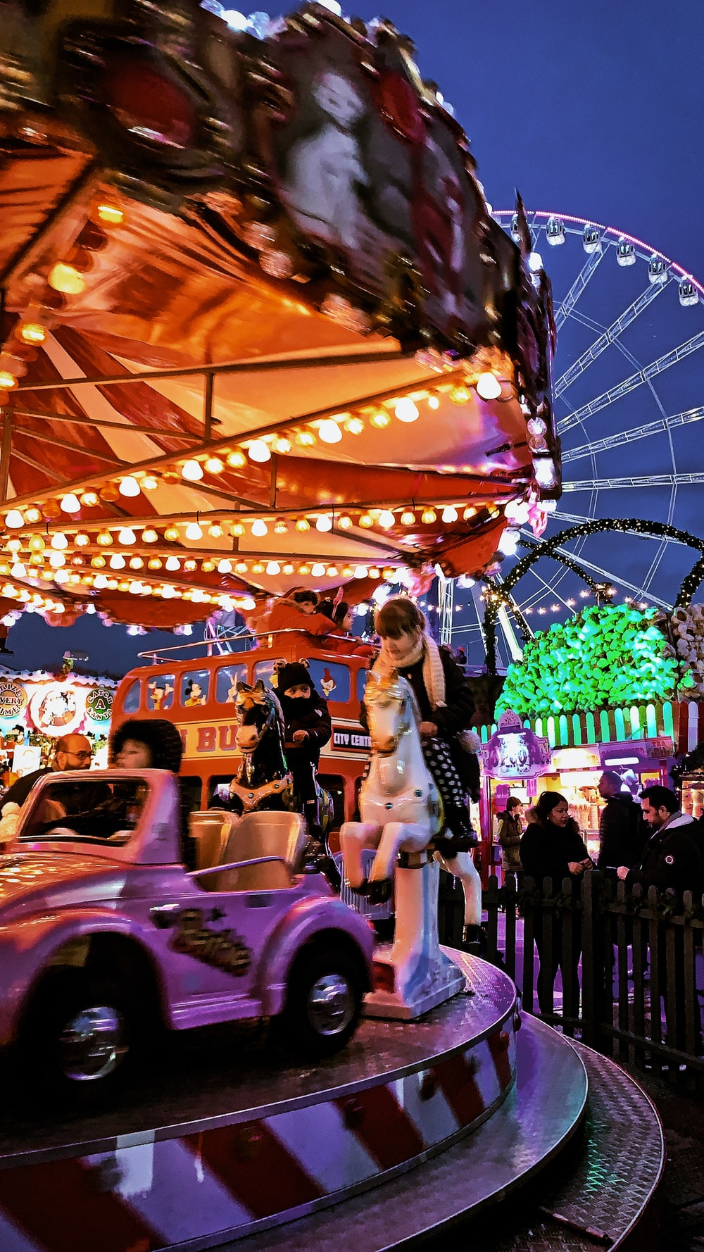 people riding on carousel during daytime