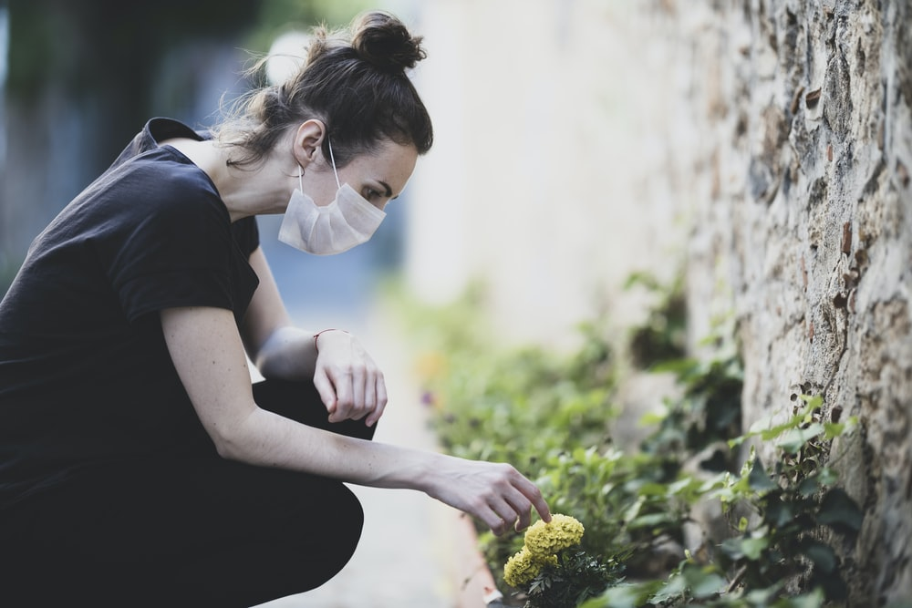 woman in black shirt holding yellow flower