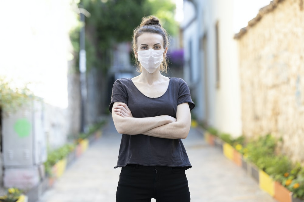 woman in black crew neck t-shirt and black pants wearing eyeglasses standing on pathway during