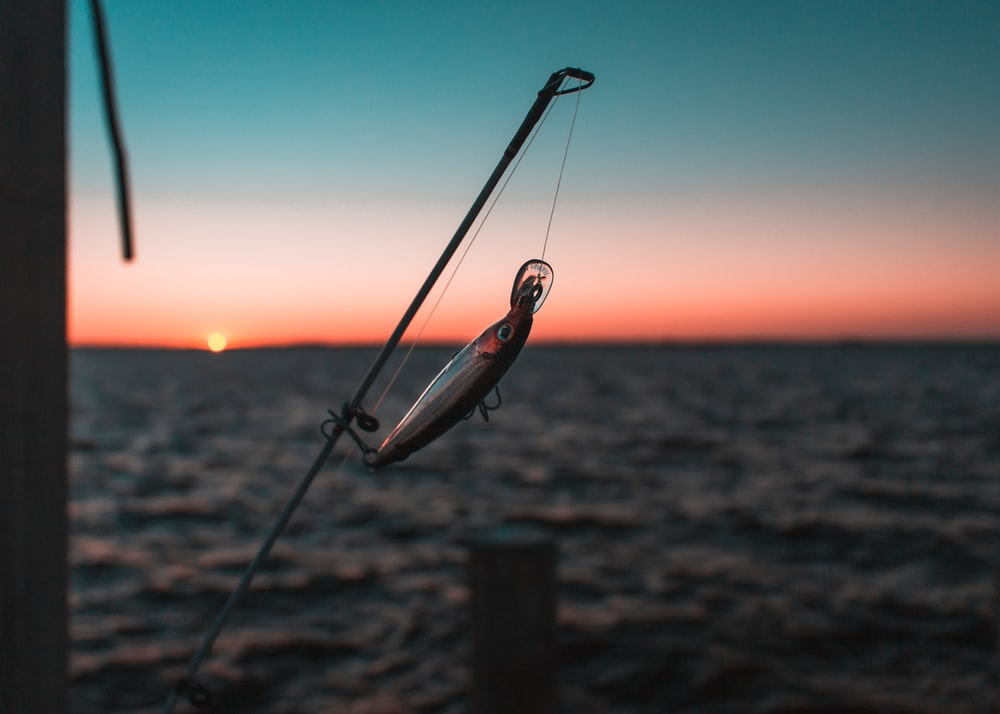 black fishing rod on brown wooden post during sunset