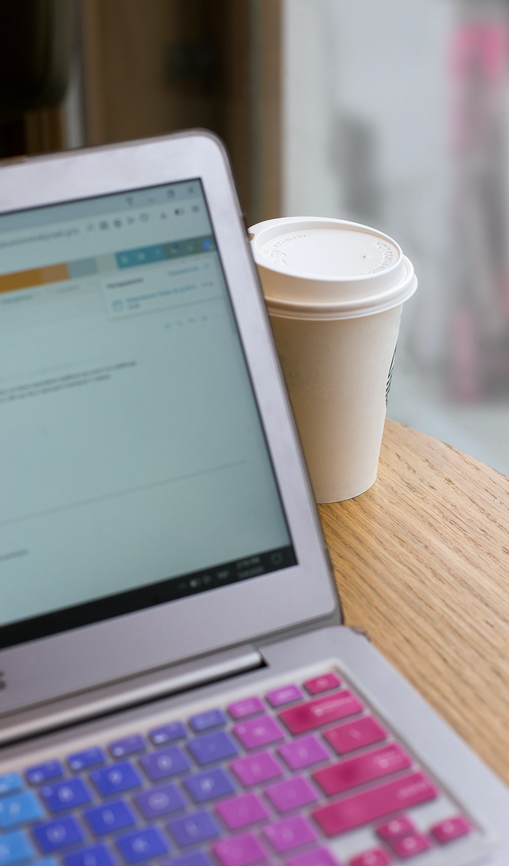 white disposable cup beside macbook air
