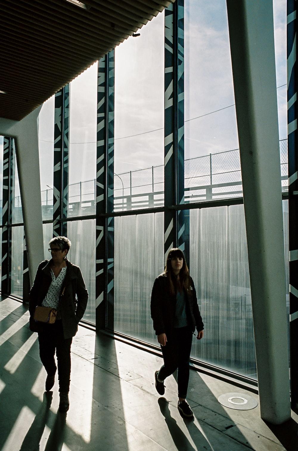 2 women standing near glass window