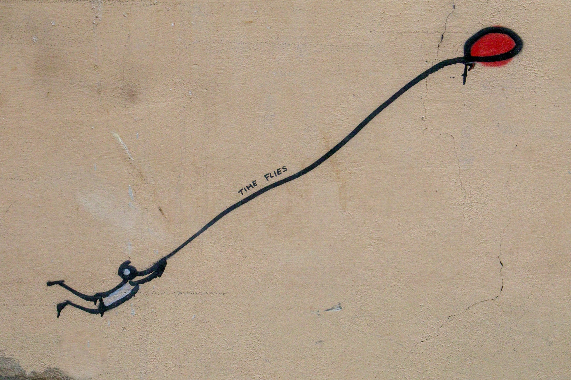 balloon graffiti pulling a stick figure with the string labeled time flies