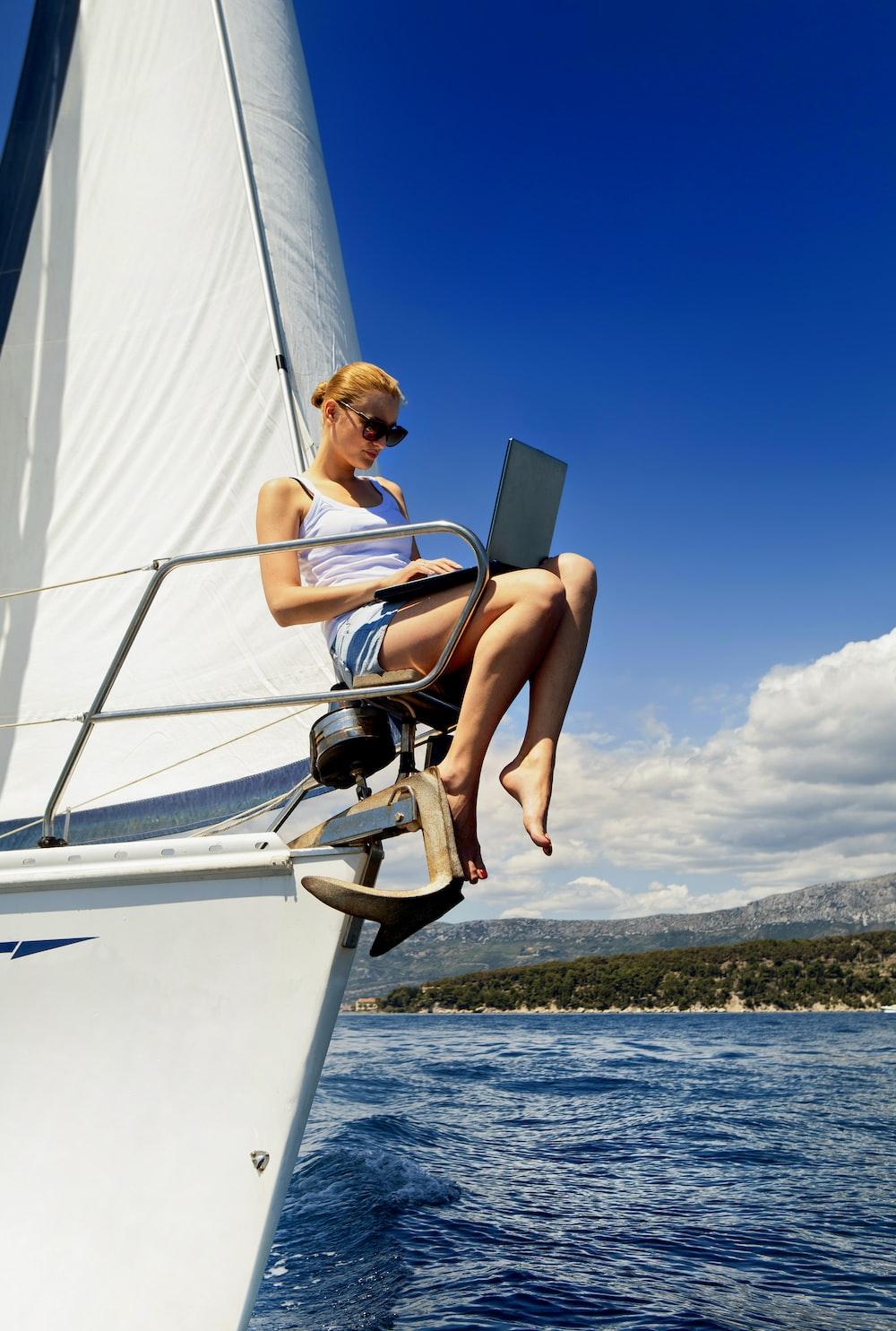 昼間に白いボートに座っている白いタンクトップの女性