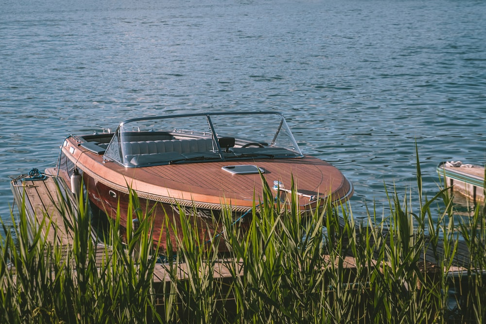 brown and white boat on body of water during daytime