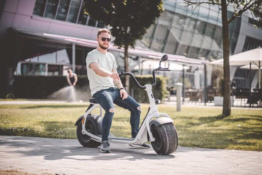 man riding with an electric scooter with a seat