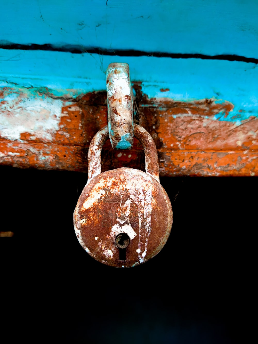 brown padlock on blue metal door