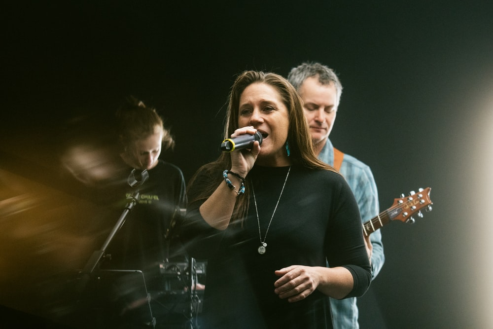 man in black crew neck t-shirt singing beside woman in gray long sleeve shirt