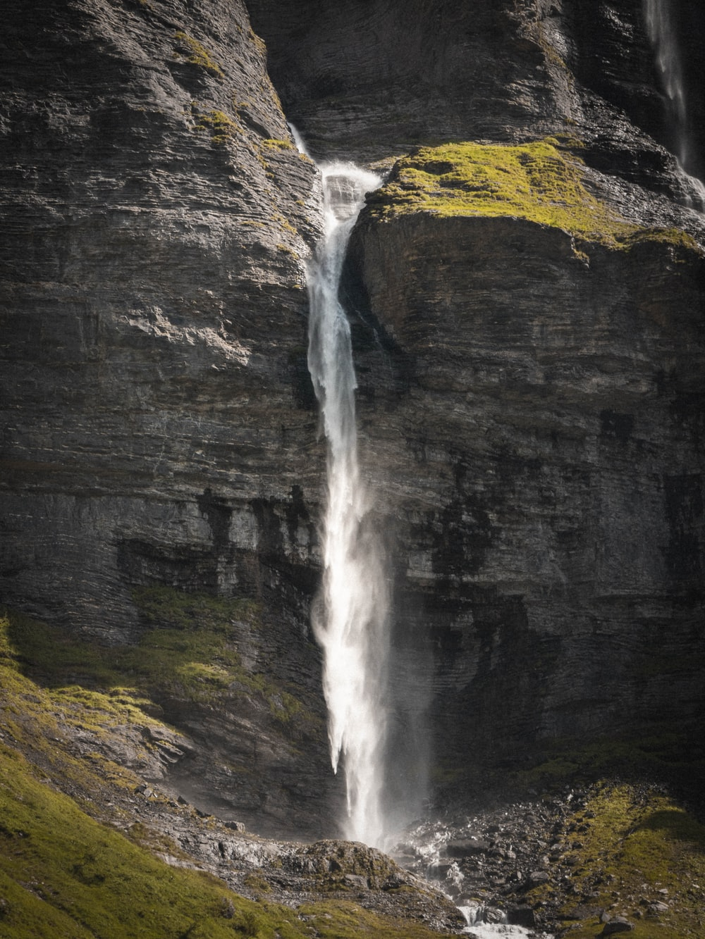 water falls on black and green mountain