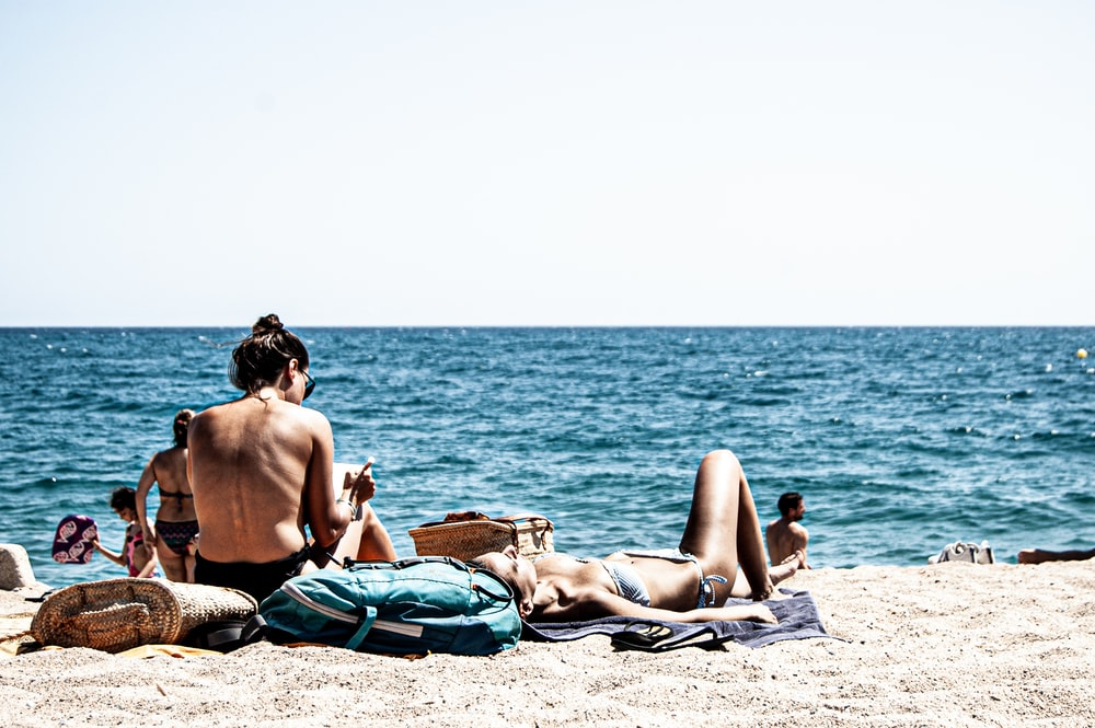 man and woman lying on beach sand during daytime