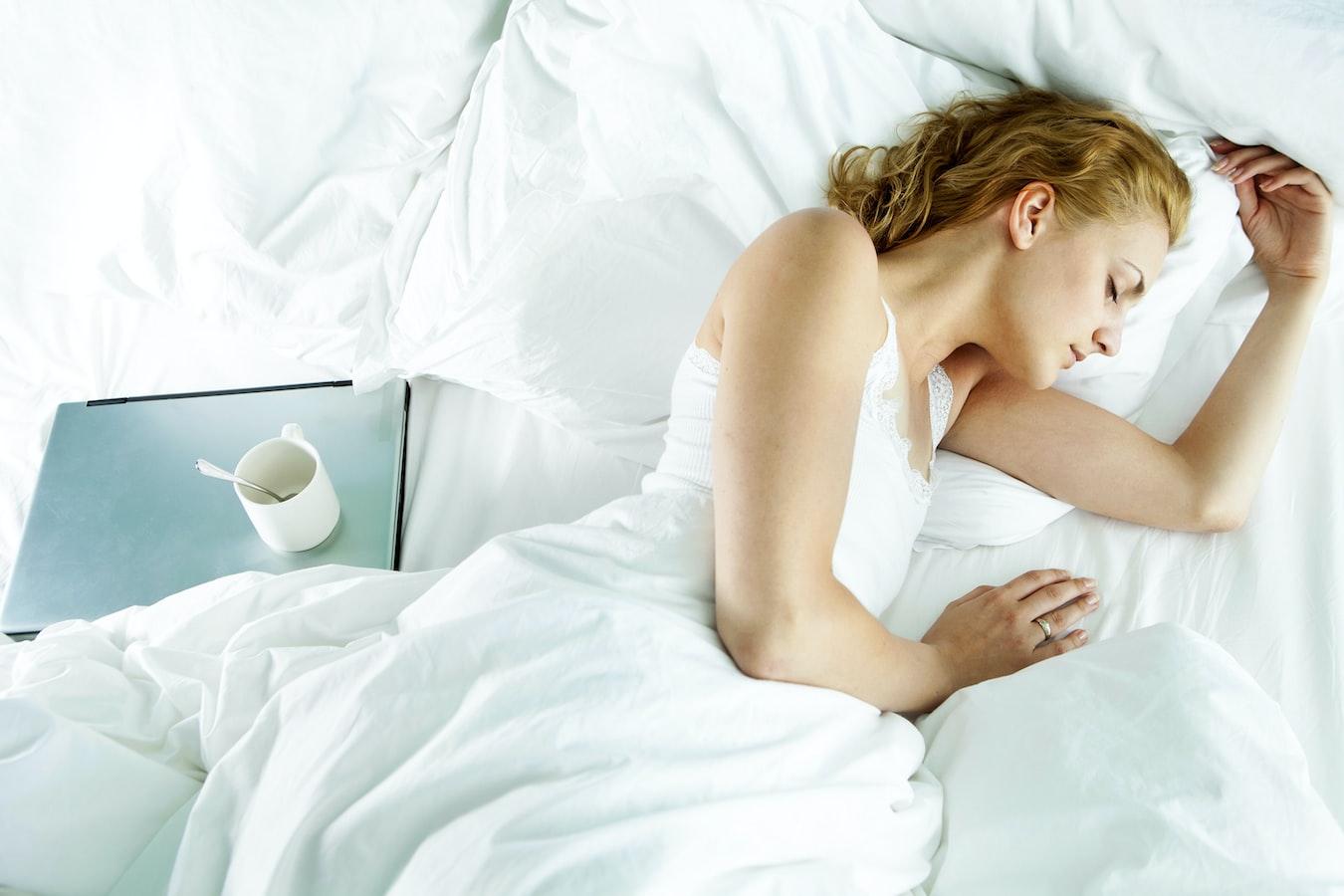 Woman sleeping next to laptop