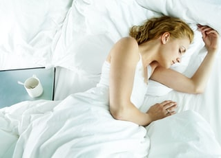 woman in white dress lying on bed