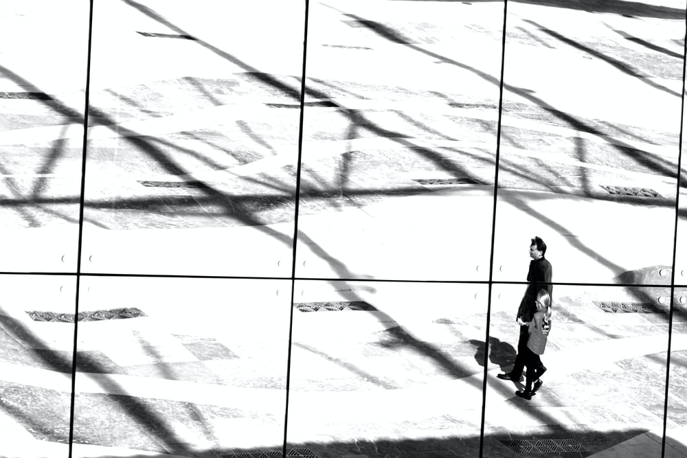silhouette of person walking on white sand during daytime