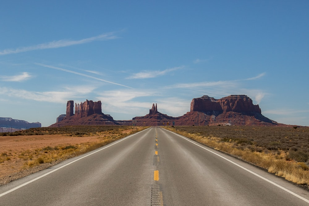 gray concrete road between brown mountains under blue sky during daytime