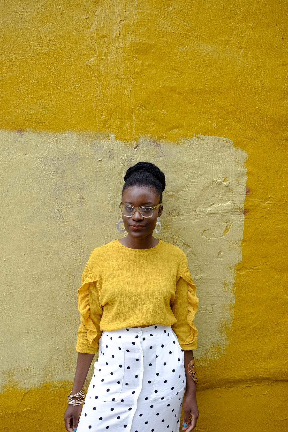woman in yellow crew neck long sleeve shirt leaning on yellow painted wall