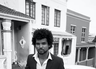 man in black suit standing beside car