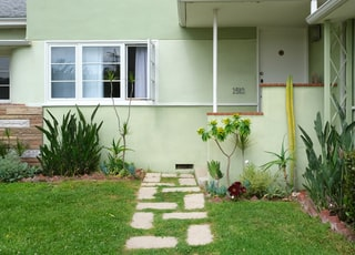 green grass lawn in front of white concrete house