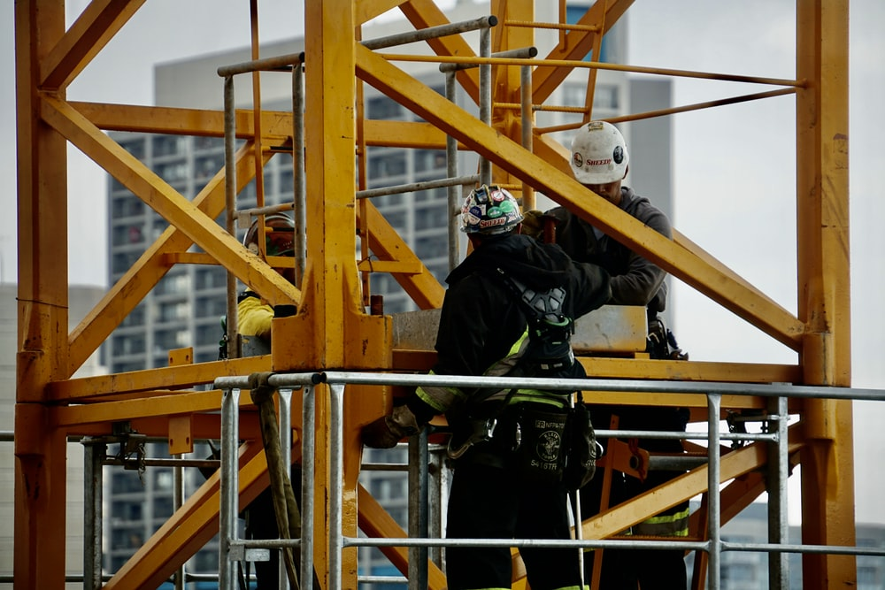 man in black jacket and helmet climbing orange ladder
