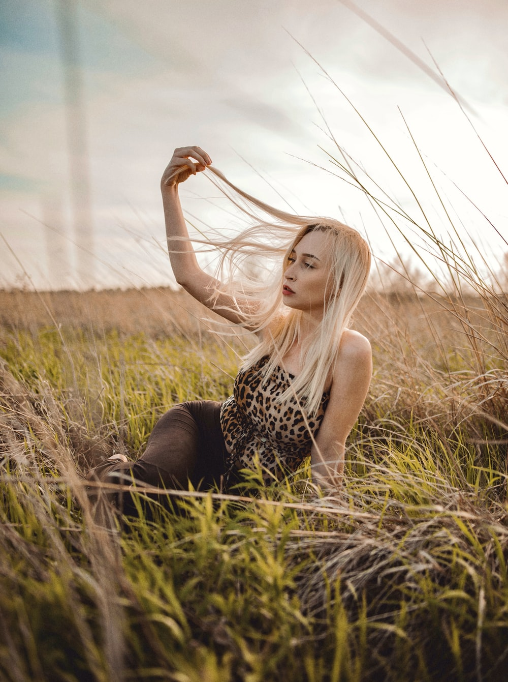 woman in black and white leopard print tank top sitting on green grass field during daytime