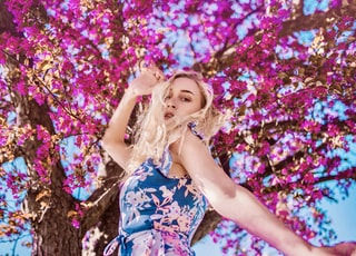 woman in blue and white floral dress lying on pink cherry blossom tree during daytime