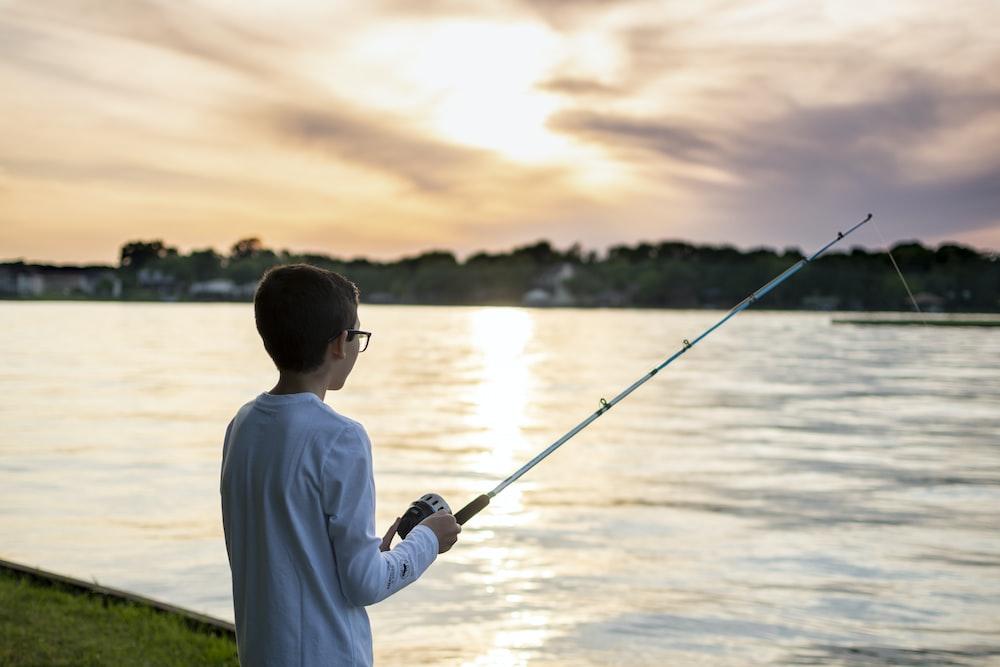 man in white long sleeve shirt holding black fishing rod