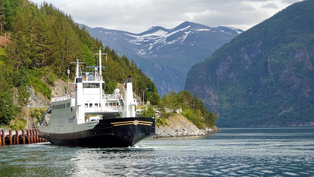 black and white ship on sea near mountain during daytime