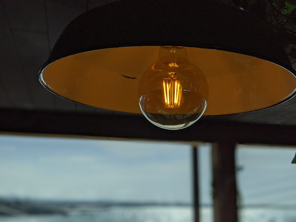 clear glass pendant lamp turned on during daytime